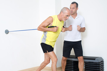 Personaltrainer erklaert Fitnessuebung mit Seilen