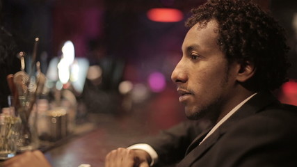 A black man sitting on a bar and smokes a cigarette