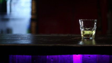 Whiskey with ice on a wooden table. Dolly shot