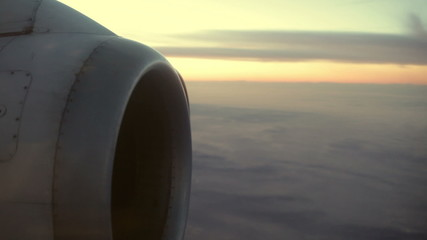 Engine detail of an airplane flying in morning sky.