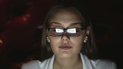 Portrait of a young woman with glasses who works at night.