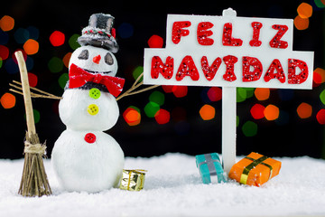 Snowman with a Merry Christmas signpost written on spanish