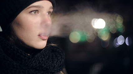 Teenager girl in the evening smoking electronic cigarette.
