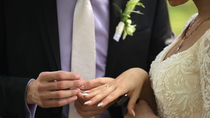 The bride and groom wear wedding rings to each other