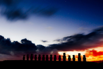 Silhouettes of fifteen moais against starry blue sky in Easter I