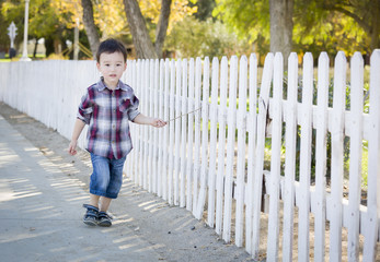 Young Mixed Race Boy Walking with Stick Along White Fence