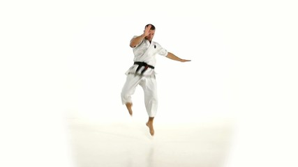 Karate. Man in a kimono hits foot on the white background. Slow