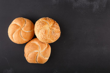 kaiser bread on dark chalkboard