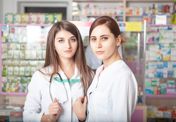 Two pharmacist greating the clients