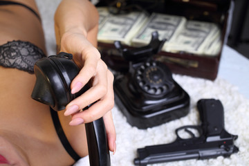sexy woman with a suitcase of money talking on the phone