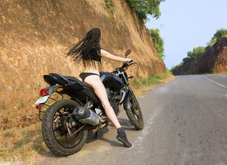 Biker theme: beautiful woman with sexy body posing with motorbik