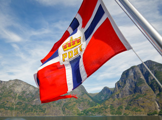 Fluttering Norwegian Post flag against fjord mountains