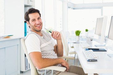 Casual young man with computer in a bright office