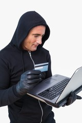 Smiling thief in hood jacket using laptop and credit card