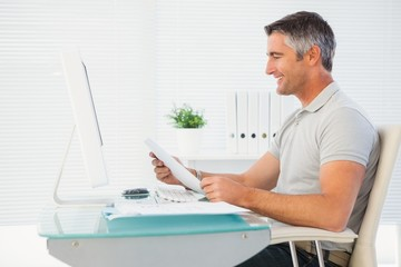 Happy man reading document at desk