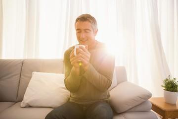 Smiling man enjoying hot drink