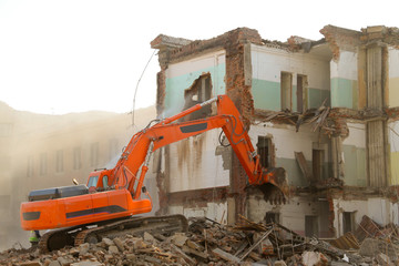 Excavator destroys old house.