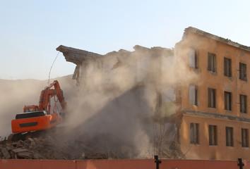 Excavator destroys old house.