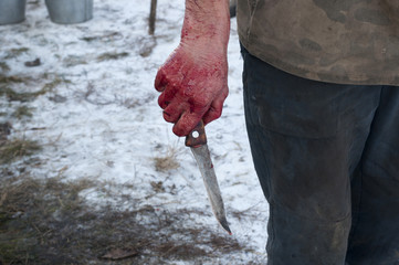 Hand holding knife with blood