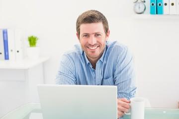 Smiling businessman holding mug at desk