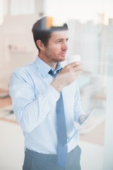 Businessman holding disposable cup and tablet