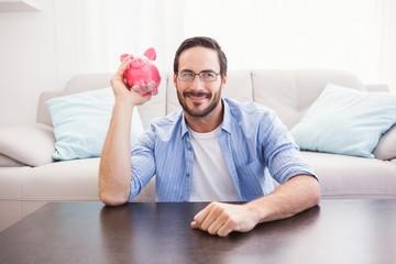 Happy man shaking a pink piggy bank