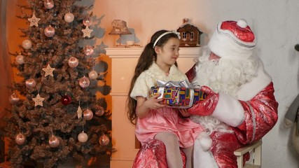 Little beautiful girl getting present from Santa Claus. Looking