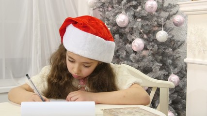 Pretty girl in Santa hat writes letter to Santa near christmas