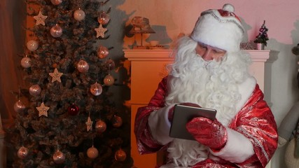 Santa Claus using tablet computer to surf internet and