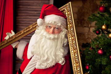 Santa Claus having fun with golden frame near  Christmas tree