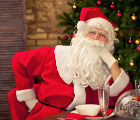 Santa Claus having fun with golden frame near  Christmas tree