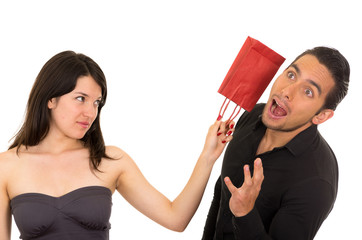 young disappointed woman hits man with gift bag