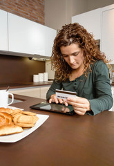Woman with electronic tablet reviewing credit card payouts