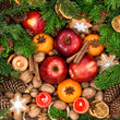 Christmas decoration with candles. Fruits, nuts, spices and cook