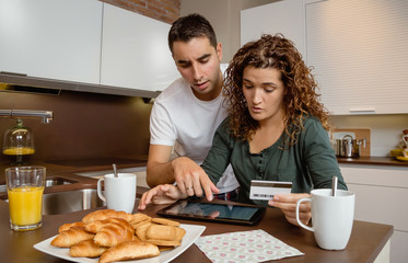 Couple with electronic tablet reviewing credit card payouts