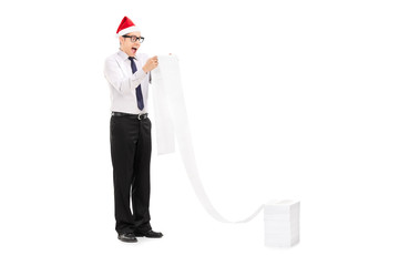 Excited man with Santa hat reading a long list
