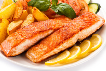Grilled salmon and vegetables on white background