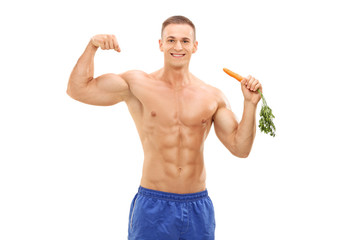 Muscular man holding a carrot and showing bicep