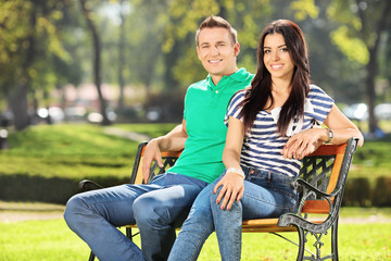 Young couple sitting on a bench in park