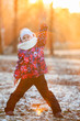 Child standing in rays of setting sun with raised hand, winter