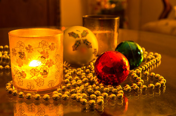 Christmas shiny colored decorations and candle in a glass