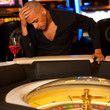 Young man playing roulette in casino betting and loosing money
