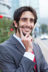 Lachender Geschäftsmann mit Bart vor Bürogebäude