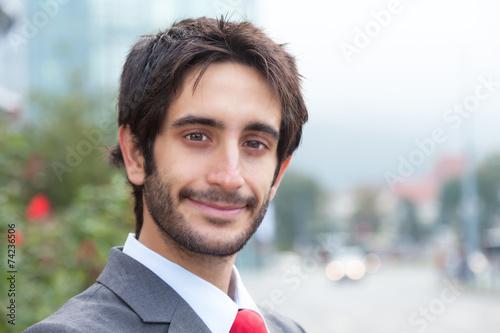 canvas print picture Sympathischer Geschäftsmann mit Bart vor Bürogebäude