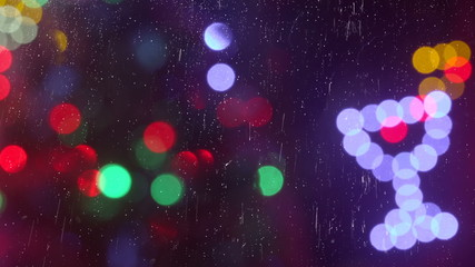 Christmas holiday out of focus lights behind a window in a rainy