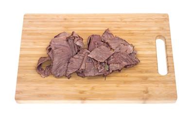 Thin sliced chuck roast on a wood cutting board
