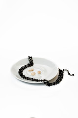 Black necklace of small beads on a saucer