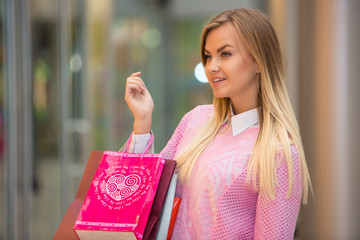 beautiful young woman goes shopping in mall