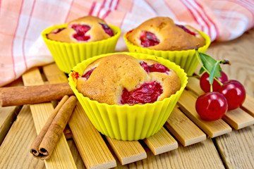 Cupcakes with cherries in tins on board