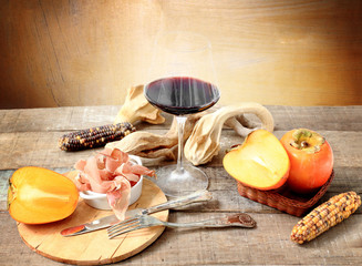 winter gourmet composition with red wine, persimmon, Parma ham,s